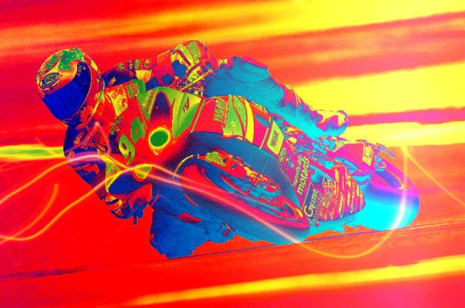 Picture of motorcycle racer on bike that is lying close to the track
